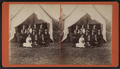 Group portrait of campers in front of a tent, by E. M. Johnson.png