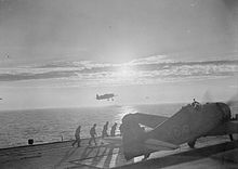Black and white photograph of a single-engined monoplane on the wooden deck of an aircraft carrier with four men walking along the deck towards the aircraft. Another aircraft is flying above the sea in the background to the photo.