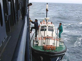 Maritime pilot - A pilot boarding a ship from a pilot boat while underway