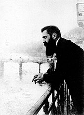 A long-bearded man in his early forties leaning over a railing with a bridge in the background.