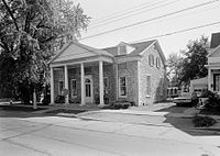 A black and white photograph of the same building from roughly the same angle. Part of another house is visible to the right.