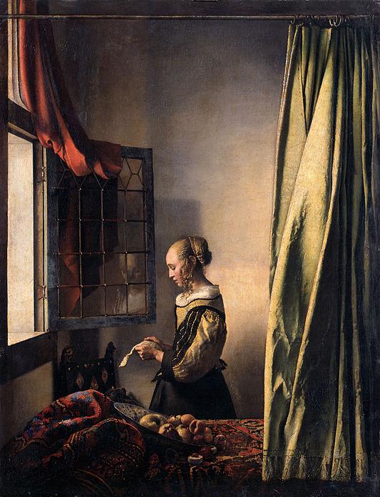 窓辺で手紙を読む若い女