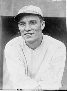 A black-and-white image of a smiling man wearing a pinstriped crownless baseball cap and a white baseball jersey