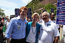 "Two older men and an older woman stand in a crowd with signs reading ""Joe Kennedy for Congress""."