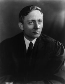 Black and white photograph; a man wearing a judge's robe looks off to the right
