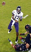 An African-American man wearing a white football jersey emblazoned with number 17 and purple pants throws a pass; the hands of various defenders are visible.
