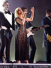 Minogue cantando en el escenario con un vestido marrón rodeado de bailarines con esmoquin