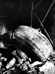 Black and white photograph of aircraft landing gear found amid debris.