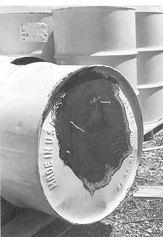Nuclear and radiation accidents and incidents - Corroded and leaking 55-gallon drum, for storing radioactive waste at the Rocky Flats Plant, tipped on its side so the bottom is showing.