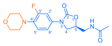 Skeletal formula of N-{[(5S)-3-[3-fluoro-4-(morpholin-4-yl)phenyl]-2-oxo-1,3-oxazolidin-5-yl]methyl}acetamide, highlighting the morpholino and fluoro groups in orange, with the rest in blue. The carbon atoms of the parent chain are numbered.