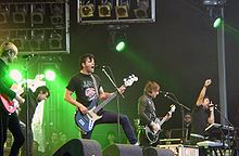 Five musicians playing, from left to right, guitar, vocals, guitar/vocals, bass, keyboard/vocals. They play with green lights in the background and large unused spotlights above their heads.