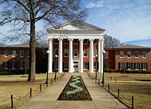 A brick building with white ionic columns in the center