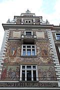 Une façade à pignons, peinte, à dominante rouge, vue en contreplongée.