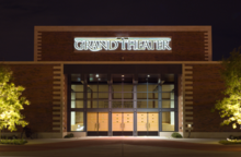 "A nighttime photograph of a building that says ""Grand Theater"" across the front."