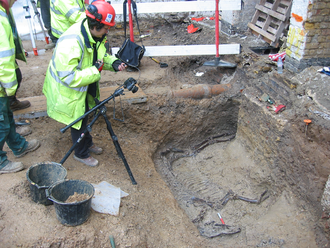 Cut (archaeology) - Photographer takes a record shot of a horse burial in a Roman ditch re-cut