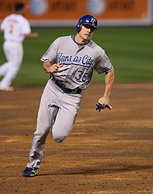 "A man in a gray baseball uniform with ""KANSAS CITY 35"" on the chest and a blue batting helmet runs on the infield dirt of a baseball field."