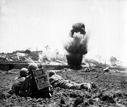 A Marine demolition crew watch explosive charges detonate and destroy a Japanese cave.
