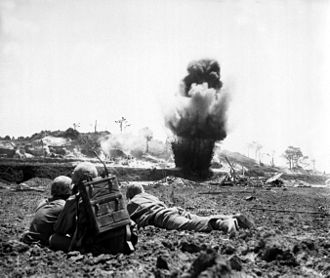 Battle of Okinawa - A 6th Marine Division demolition crew watches explosive charges detonate and destroy a Japanese cave, May 1945.