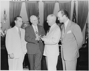 Photograph of President Truman in the Oval Office, receiving a gold pass to all games of the All-America Football... - NARA - 200170.tif
