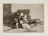 Huddled behind the ruins of a building, two women, one with a child in her arms, lay a third to her permanent rest in the ground. To the rear another woman lies dead.