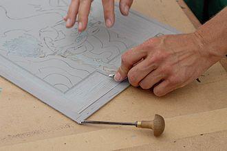 Linocut - Using a handheld gouger to cut a design into linoleum for a linocut print