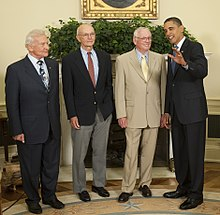 The astronauts are all elderly but standing straight. Aldrin wears a dark suit, Collins a dark sportcoat and gray pants, and Armstrong a beige suit, the President is at the right. He wears a dark suit, he has medium-dark skin and is talking to Armstrong and raising his left hand. Armstrong is smiling.