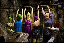 A group of 6 women wearing ski masks and multicolored clothes in a small, grubby brick space. Four of them hang by their arms from a bar, one flexes her muscles, and another grabs one of the hanging women around the waist.