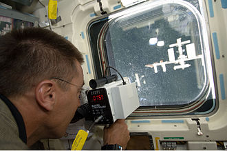 Space rendezvous - Astronaut Christopher Cassidy uses a rangefinder to determine distance between the Space Shuttle ''Endeavour'' and the International Space Station
