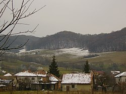 A picturesque view of Recea-Cristur with snow powdered cottages and hills.