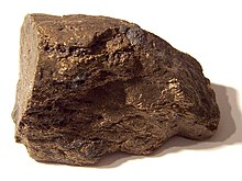 A brown block of irregular shape and surface, about 6 cm in size.