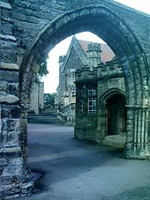 A school viewed through a stone gateway