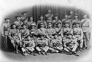 A formative photograph of white soldiers in African colonial-style uniforms, arranged in four rows; two standing, one sitting on chairs and one sitting on the floor