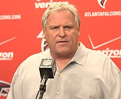 Candid photograph of Smith standing before a podium with a red backdrop bearing logos of the Atlanta Falcons and Verizon behind him