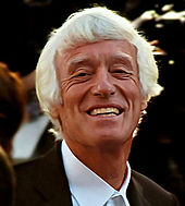 An older man with medium-length white hair and tanned skin smiles at the camera.