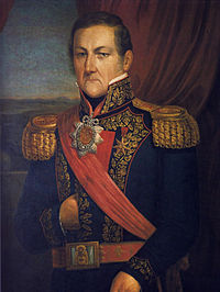 Half-length painted portrait of an older man with aquiline nose and stern expression wearing an elaborately embroidered military tunic with heavy gold epaulettes and braids, a red sash and belt with a very large medal suspended on a red ribbon at the neck