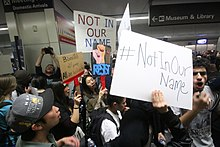 "Crowd at San Francisco International Airport. Signs are visible, some reading ""Not in our name""."