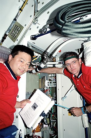 Shirt-sleeve environment - Astronauts Leroy Chiao (left) and William McArthur, who earlier shared space walk time to work on the exterior of the International Space Station (ISS), are pictured here in the shirt-sleeve environment of the Functional Cargo Block (FGB) on the station. The two mission specialists were in the process of changing out the Y-cable in the FGB.