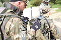 Slovenian soldiers check settings on a radio while U.S. Soldiers with Zulu Troop, 525th Battlefield Surveillance Brigade (BfSB) perform premission checks during the Kosovo Force (KFOR) 17 Mission Rehearsal 130509-A-HJ139-002.jpg