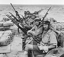 A close-up of six men in three Jeeps. A heavily armed patrol of 'L' Detachment SAS. The crews of the Jeeps are all wearing 'Arab-style' headdress, as copied from the Long Range Desert Group. Jerri cans can be seen mounted around the vehicles
