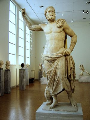 Poseidon of Melos - Frontal view of the statue in its current location in room 30 of NAMA ( in the background)