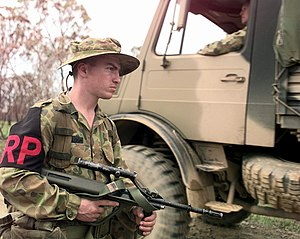 Regimental Police - Regimental Policeman of the Australian Army's 9th Royal Queensland Regiment, holding an F88 5.56mm rifle, manning a security check point during exercise Crocodile '99 in the Shoalwater Bay Training Area, Queensland, Australia.