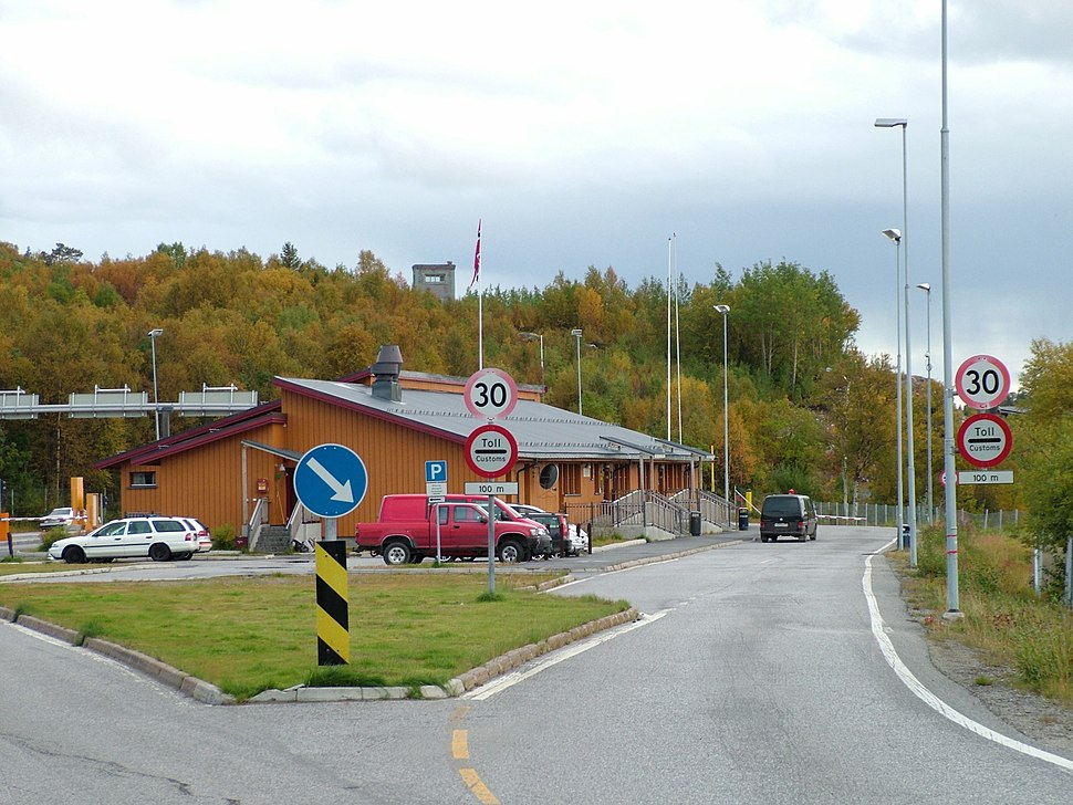 Storskog border station from the Norwegian side. Border posts are visible between the building and the dark van. Note the Russian watch tower on the hill in the background.