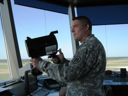 An air traffic controller holding a signal light gun that can be used to direct aircraft experiencing a radio failure (2007). TC with light gun.JPG