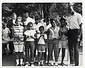 The Boston Celtics' Satch Sanders poses with a group of girls holding basketball trophies (12462122333).jpg