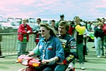 Thierry Boutsen hitches a lift from Louise Goodman in the paddock before the 1993 British Grand Prix (32843907114).jpg