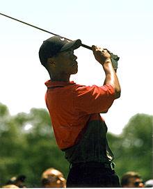 Un golfeur avec un club en main regarde au loin.