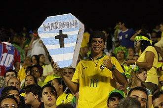 "Argentina–Brazil football rivalry - Brazilian supporter with a fake coffin with the colors of the Argentine flag and the name ""Maradona"""