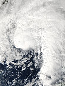 Satellite image of a comma-shaped tropical cyclone just off the United States Gulf Coast. All land in the image is obscured by cloud cover which extends in all directions, except southwest, from the center of the storm.