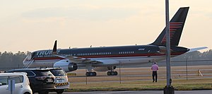 A Boeing 757 with blue, red, and white livery, idling on a runway. This plane belongs to Trump, who nicknamed it
