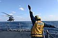 U.S. Navy Boatswain's Mate 3rd Class Brittany Chiles, assigned to the guided missile destroyer USS McCampbell (DDG 85), signals to an SH-60B Seahawk helicopter as it lands on the ship's flight deck March 4 130304-N-TG831-206.jpg